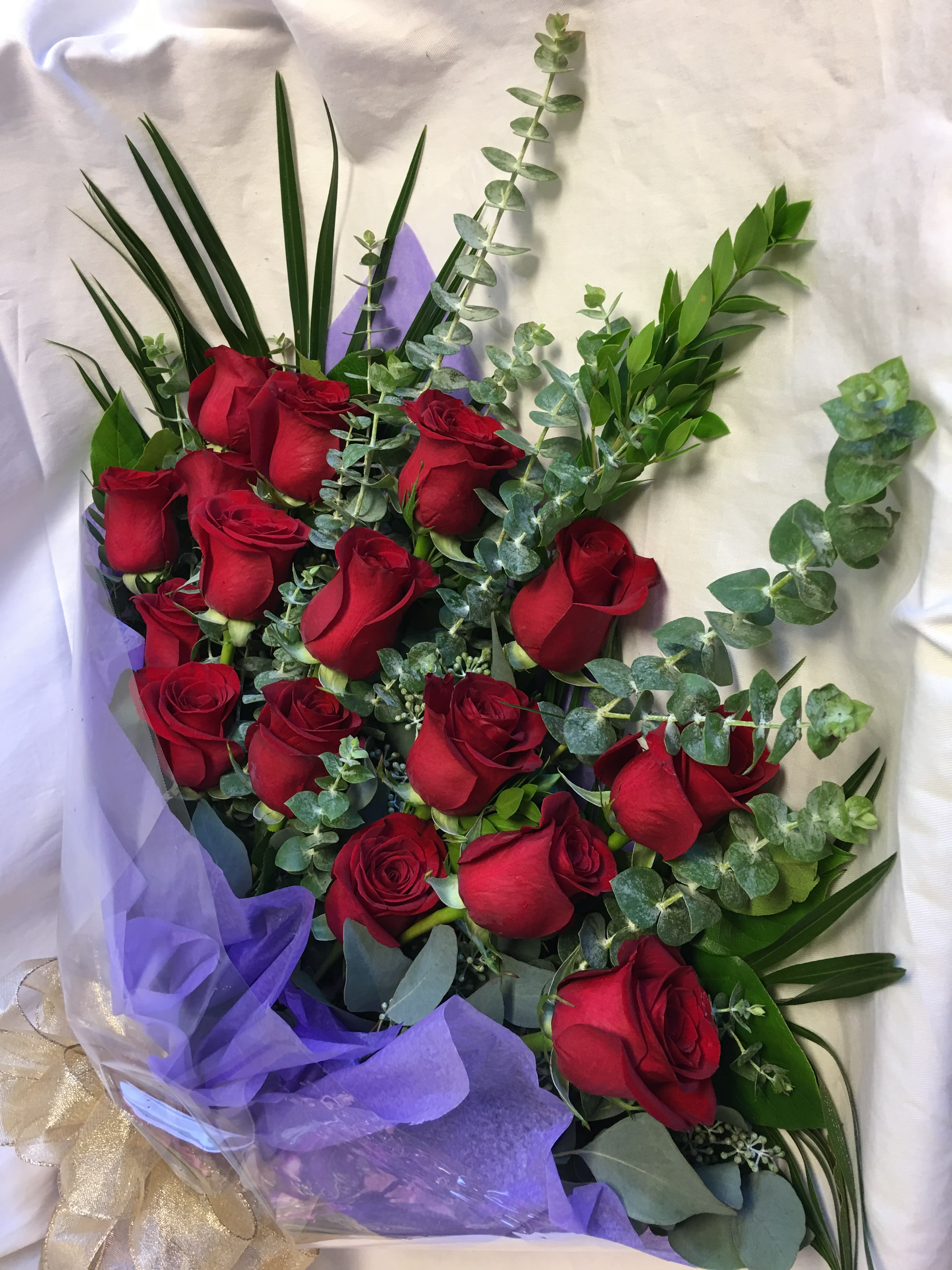LOVE PRESENTED - 15 red roses hand-tied with greenery wrapped neatly in clear cellophane. Flowers ...