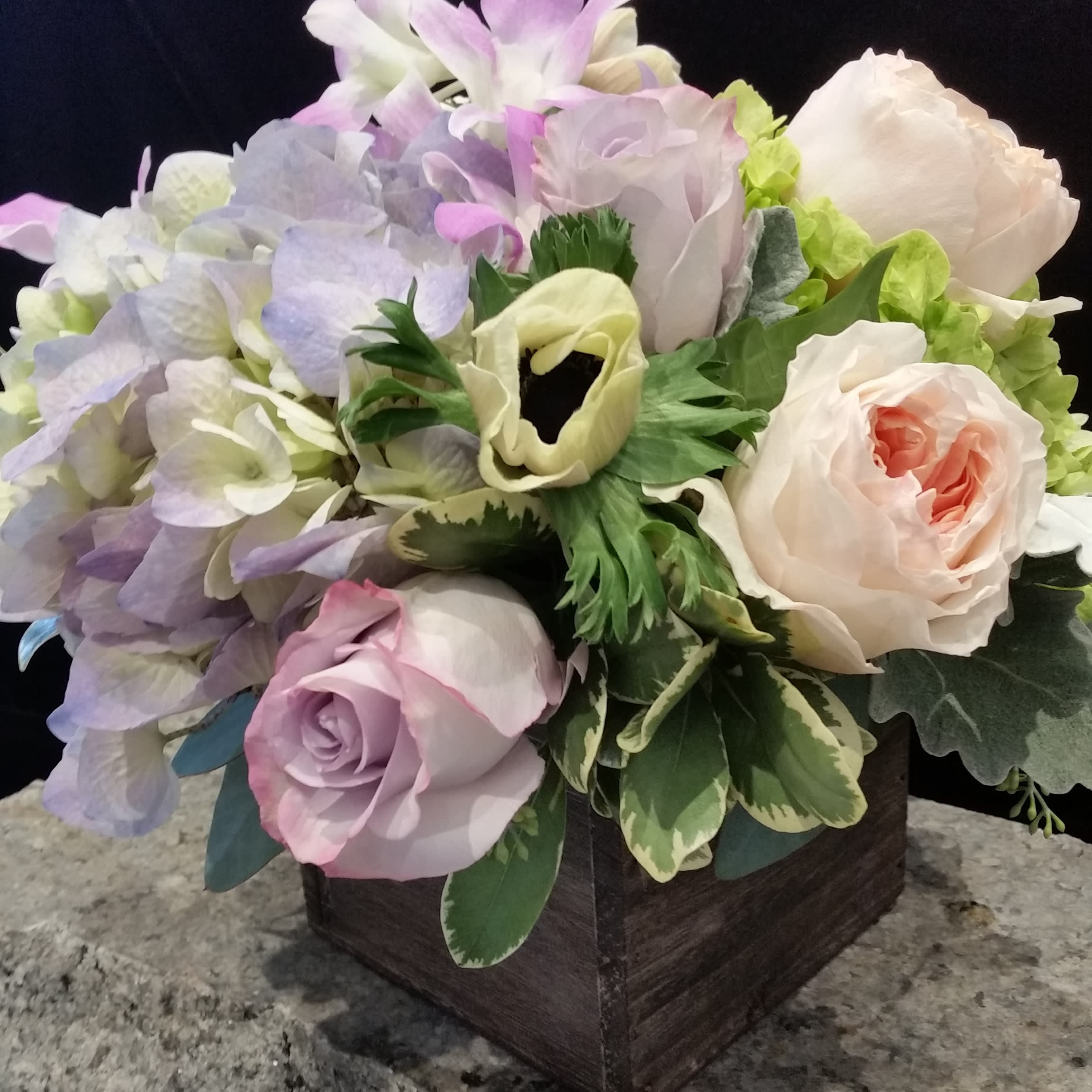 A Walk in the Woods - We have featured an enchanting mix of soft colors and natural flowers in a simple wooden cube for this arrangement called A Walk in the Woods.  'Natural' is in style. A simple wooden cube contains lavender and cream hydrangea, premium lavender and peach roses, stunning peach garden roses, and white anemone. Uncomplicated and so very pretty!